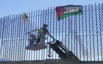 دورية اسرائيلية تعمل على نزع الأعلام التي رُفعت على السياج الحدودي